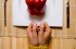 photo of two hands tied with a measuring tape in front of a plate with a bell pepper on it - Freedom Interventions - eating disorders