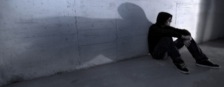 photo of a lonely man sitting against a wall with his shadow cast beside him - Freedom Interventions - who needs intervention