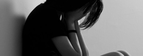 photo of an upset woman with her head in her hands - suicide in addiction - freedom interventions